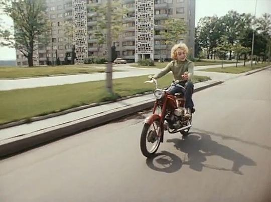 Кадр из фильма Приключения Электроника, где Электроник едет на мопеде и поет песню